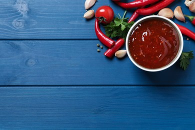 Spicy chili sauce and ingredients on blue wooden table, flat lay. Space for text