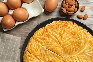 Traditional galette des rois and ingredients on wooden table, flat lay