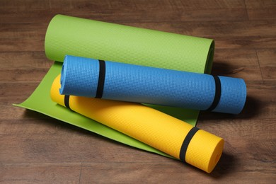 Bright camping or exercise mats on wooden background