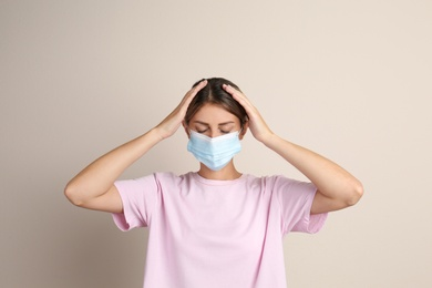 Stressed woman in protective mask on beige background. Mental health problems during COVID-19 pandemic