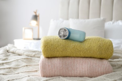 Modern fabric shaver and woolen sweaters on bed indoors