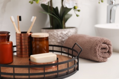 Tray with different toiletries and towel on countertop in bathroom, closeup