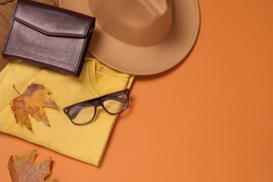 Flat lay composition with stylish hat on orange background, space for text