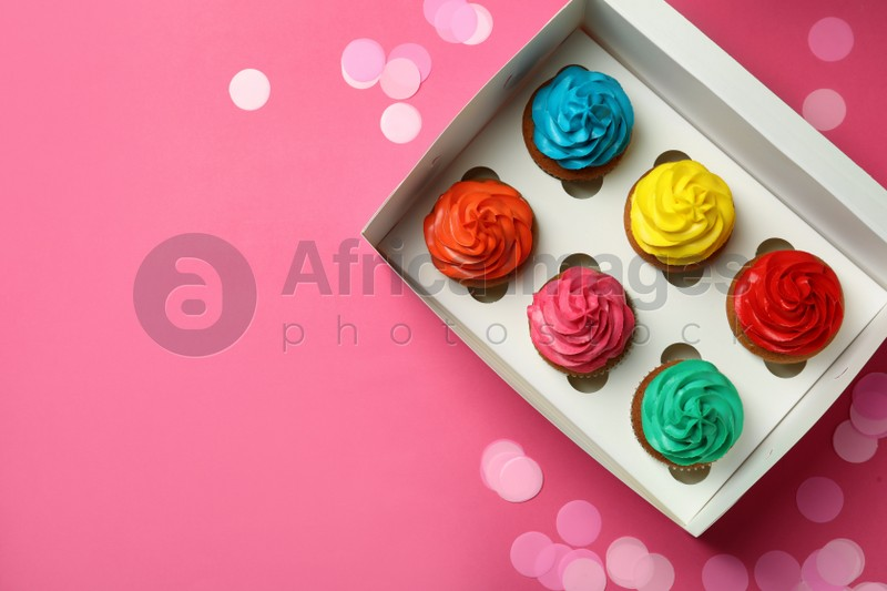 Box with different cupcakes and confetti on pink background, flat lay. Space for text