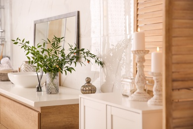Vase with beautiful branches near vessel sink in bathroom. Interior design