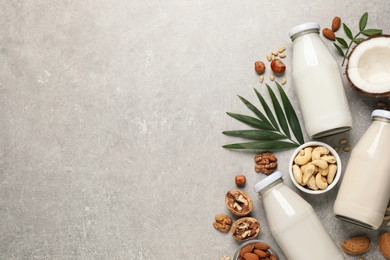 Vegan milk and different nuts on grey table, flat lay. Space for text