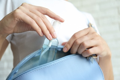 Woman putting hand sanitizer in purse on light background, closeup. Personal hygiene during COVID-19 pandemic