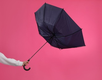 Woman with umbrella caught in gust of wind on pink background, closeup