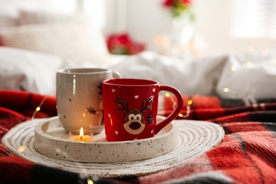 Christmas cups in tray on red woolen blanket. Interior decor