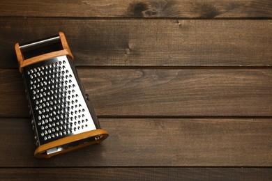 Modern grater on wooden table, top view. Space for text