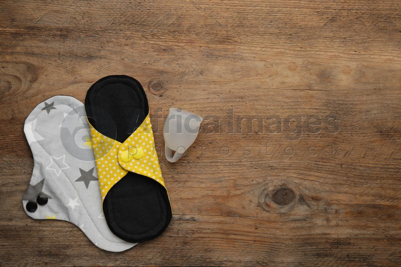 Reusable cloth pads and menstrual cup on wooden table, flat lay. Space for text
