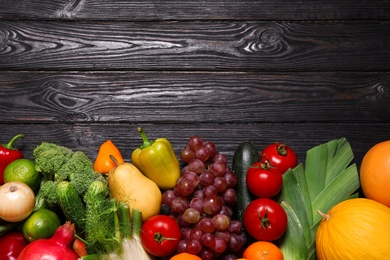Assortment of fresh organic fruits and vegetables on black wooden table, flat lay. Space for text
