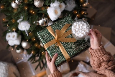 Woman with cup of delicious hot drink and gift box near Christmas tree at home, top view