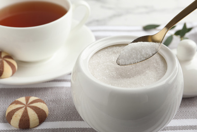 Spoon with granulated sugar over bowl on table