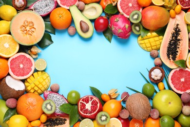 Frame of different exotic fruits on light blue background, flat lay. Space for text