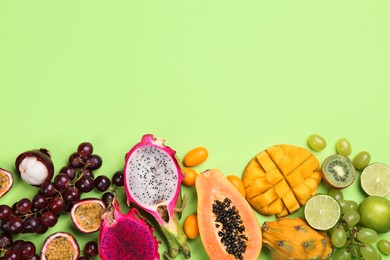 Many different delicious exotic fruits on green background, flat lay. Space for text