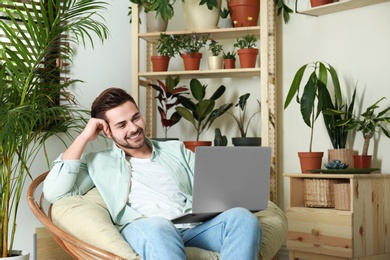 Young man using laptop in room with different home plants