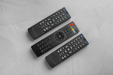Modern tv remote controls on grey table, flat lay