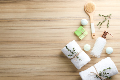 Flat lay composition with soap dispenser on wooden background. Space for text