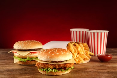 Delicious fast food menu on wooden table against red background