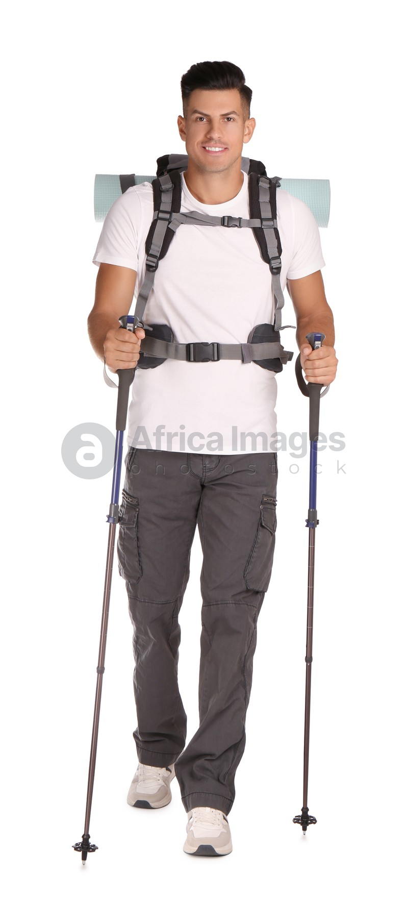Male hiker with backpack and trekking poles on white background