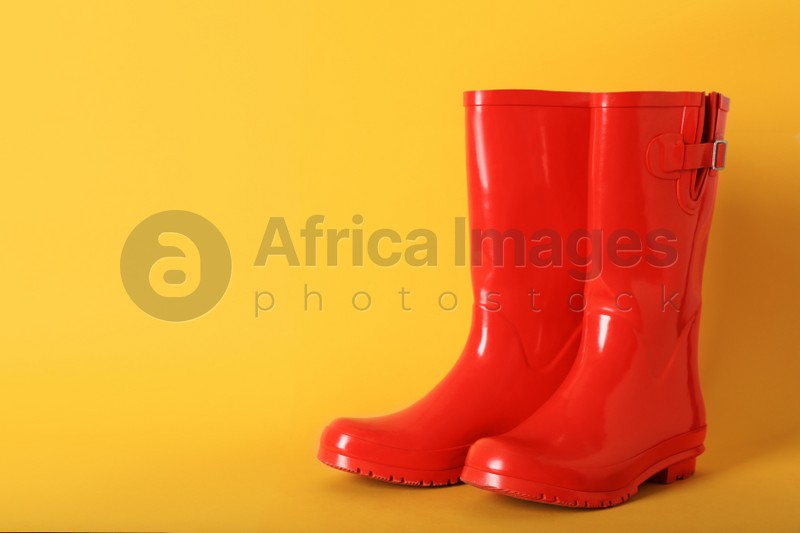 Pair of red rubber boots on orange background. Space for text