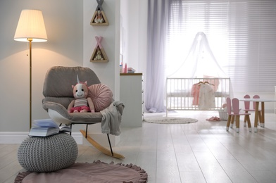 Cozy baby room interior with comfortable rocking chair