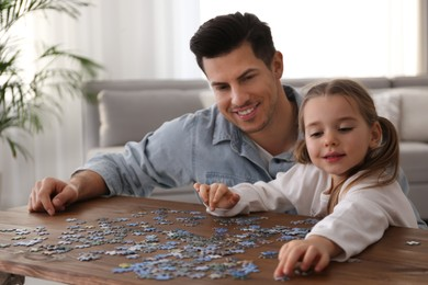 Man and his little daughter playing with puzzles at home