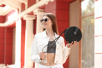 Beautiful young woman with stylish handbag outdoors on summer day
