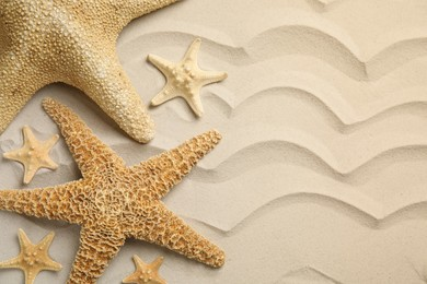 Beautiful sea stars on sand, flat lay. Space for text
