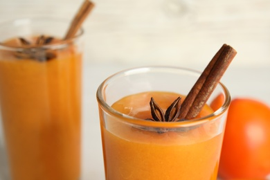 Tasty persimmon smoothie with anise and cinnamon, closeup