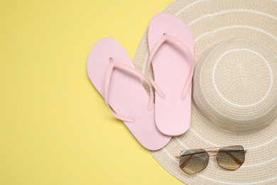 Flip flops, hat and sunglasses on yellow background, flat lay with space for text. Beach objects