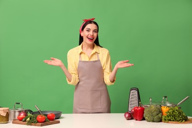 Emotional housewife at white table with vegetables and different utensils on green background