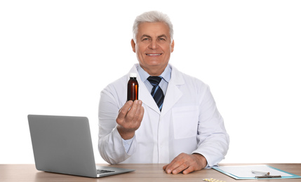 Professional pharmacist with syrup and laptop at table against white background