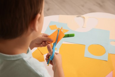 Little boy cutting color paper with scissors at table indoors, closeup