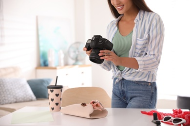 Young photographer taking picture of accessories indoors, closeup