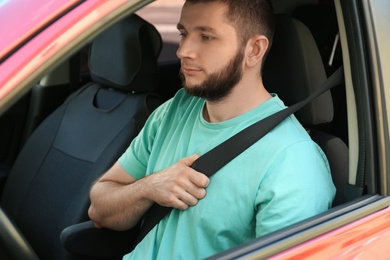 Man with fastened safety belt on driver's seat in car