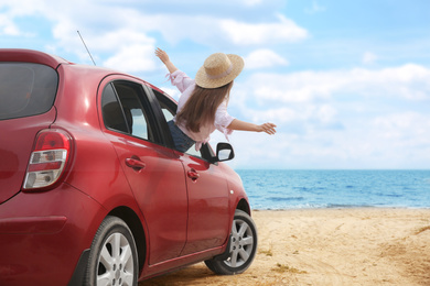 Happy woman leaning out of car window on beach. Summer vacation trip