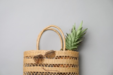 Stylish straw bag and sunglasses on grey background, flat lay. Summer accessories