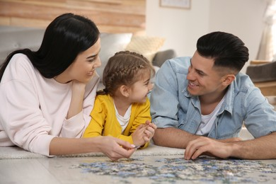 Happy family playing with puzzles on floor at home