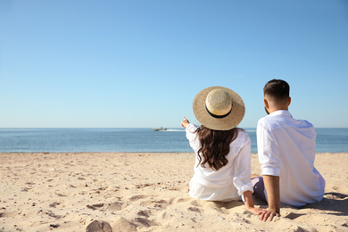 Young couple on beach near sea, back view. Honeymoon trip