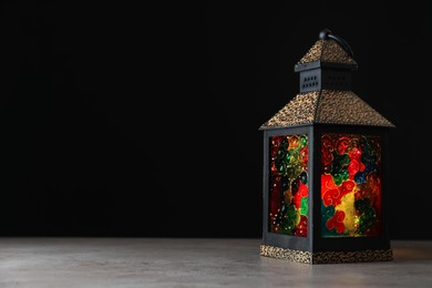 Decorative Arabic lantern on grey table against black background, space for text