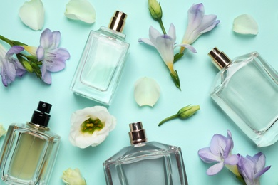 Flat lay composition of different perfume bottles and flowers on cyan background