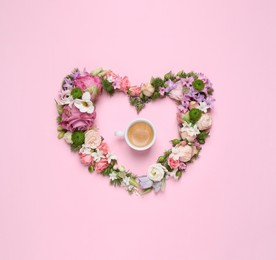 Beautiful heart made of different flowers and coffee on pink background, flat lay