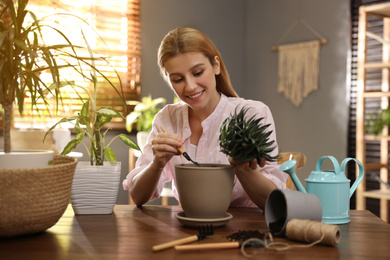 Young woman potting succulent plant at home. Engaging hobby