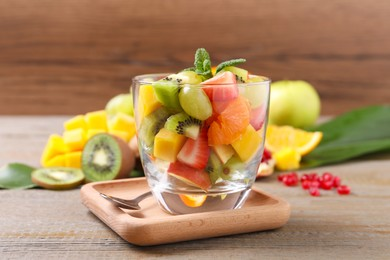 Delicious fresh fruit salad in dish on wooden table