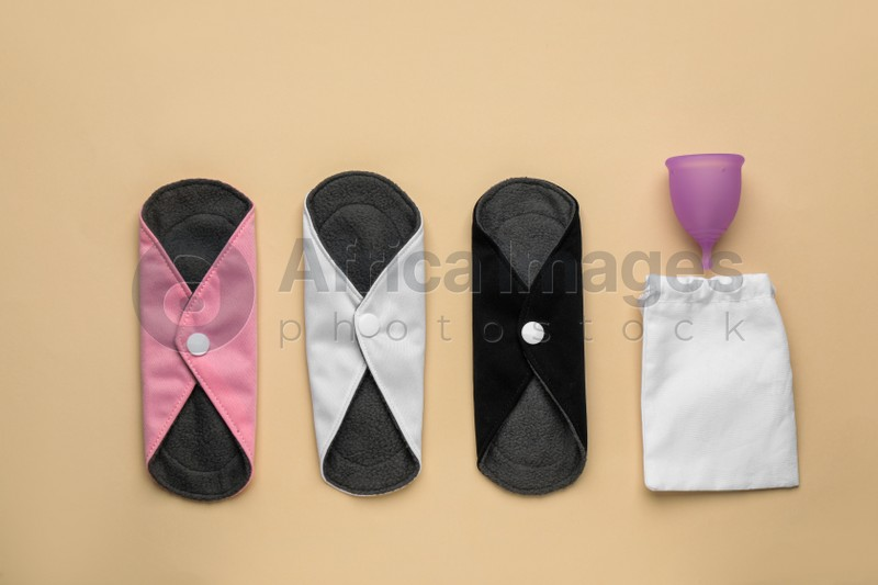 Different reusable cloth pads and menstrual cup on beige background, flat lay