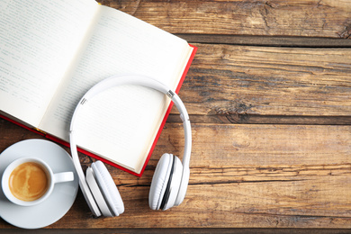 Book, coffee and headphones on wooden table, flat lay. Space for text