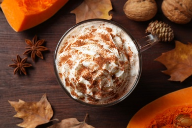 Delicious pumpkin latte on brown table, top view