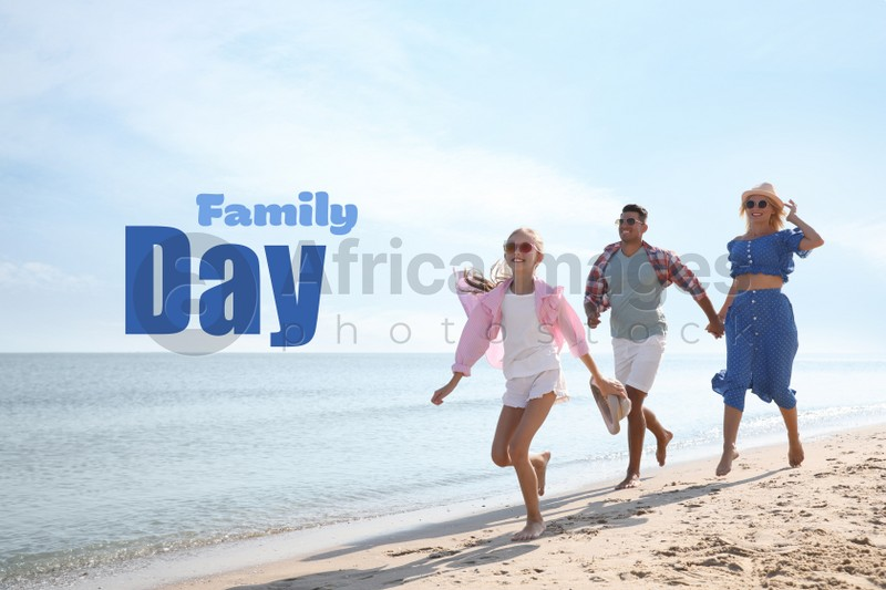 Happy parents and their daughter on sandy beach near sea. Happy Family Day